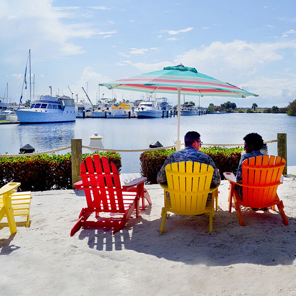 People sitting waterfront by a marina