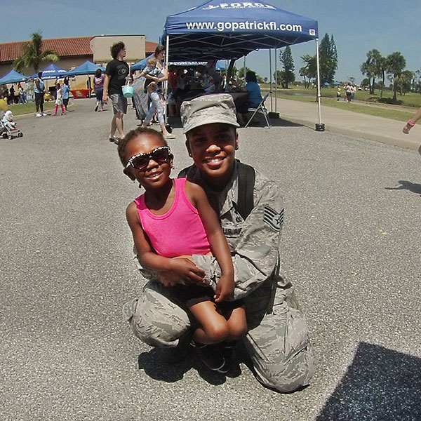 Soldier holding a child at Air Force event